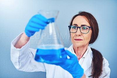 Buy stock photo Studio shot of a mature scientist conducting an experiment against a blue background