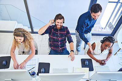 Buy stock photo High angle shot of a team of young people working in a call centre