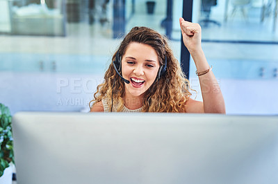 Buy stock photo Shot of a young woman cheering at her desk while working together in a call centre
