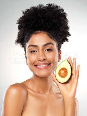 Buy stock photo Studio portrait of a beautiful young woman holding an avocado while posing against a gray background