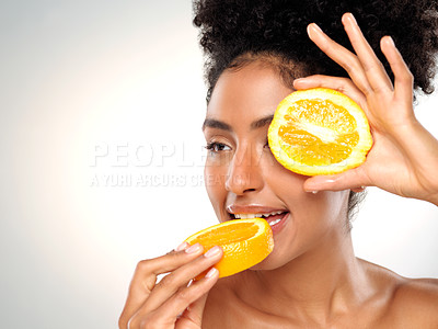 Buy stock photo Studio shot of a beautiful young woman holding an orange while posing against a gray background