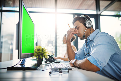Buy stock photo Cropped shot of a handsome young man looking stressed while working in a call center
