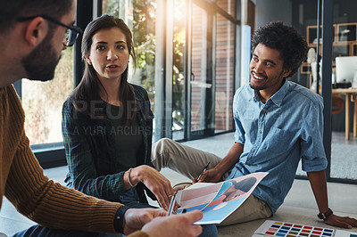 Buy stock photo Shot of a team of designers brainstorming on the floor in an office