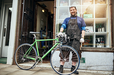Buy stock photo Shot of a handsome man standing outside of his self-owned bicycle shop
