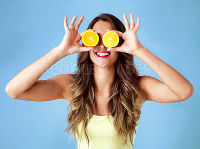 Buy stock photo Studio shot of a young woman covering her eyes with oranges against a blue background