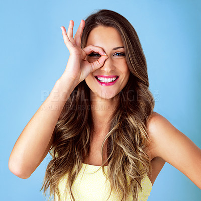 Buy stock photo Studio shot of a beautiful young woman looking through her finger against a blue background