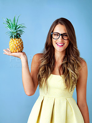 Buy stock photo Studio shot of a young woman holding a pineapple against a blue background