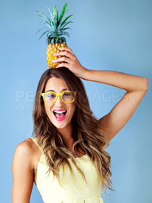 Buy stock photo Studio shot of a young woman balancing a pineapple on her head against a blue background