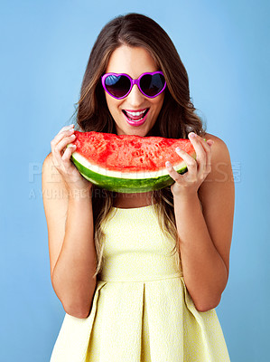 Buy stock photo Studio shot of a beautiful woman holding a watermelon against a blue background