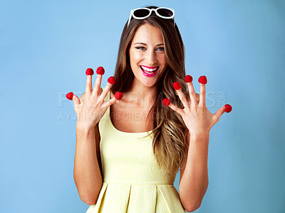 Buy stock photo Studio shot of a woman posing with raspberries on her fingertips against a blue background