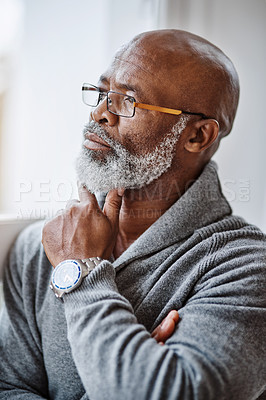 Buy stock photo Shot of a handsome senior man looking thoughtful while relaxing at home