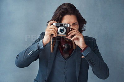 Buy stock photo Studio shot of a stylishly dressed handsome young man taking a picture with a vintage camera