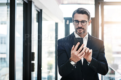 Buy stock photo Shot of a mature businessman using a smartphone in a modern office