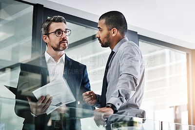 Buy stock photo Shot of two businessmen discussing paperwork in a modern office