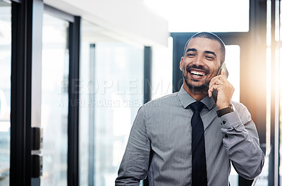 Buy stock photo Shot of a young businessman using a smartphone in a modern office