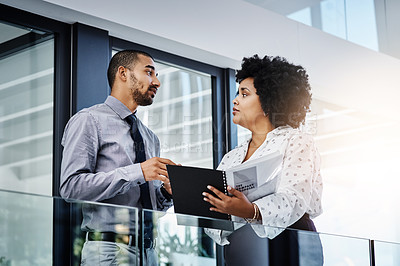 Buy stock photo Shot of a businessman and businesswoman discussing paperwork in a modern office