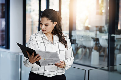 Buy stock photo Shot of a young businesswoman going over paperwork in a modern office
