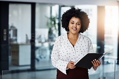 Buy stock photo Portrait of a young businesswoman going over paperwork in a modern office