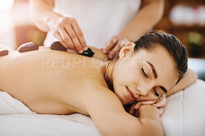 Buy stock photo Shot of a young woman getting hot stone therapy at a spa