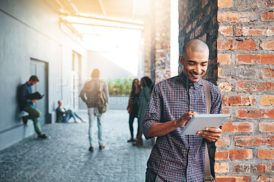 Buy stock photo Shot of a young man using a digital tablet outdoors on campus