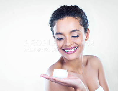 Buy stock photo Studio shot of a beautiful young woman holding a tub of moisturiser