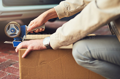Buy stock photo Closeup shot of a courier sealing a ox with tape for delivery