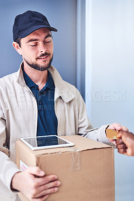 Buy stock photo Shot of a courier accepting a credit card payment from a customer for a delivery