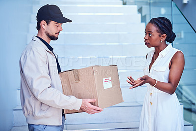Buy stock photo Shot of a businesswoman looking upset with her delivery from the courier