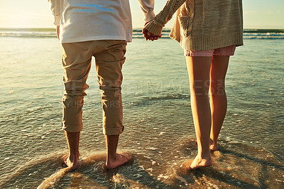 Buy stock photo Rearview shot of an unrecognizable young couple standing hand in hand on the beach