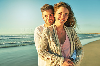 Buy stock photo Cropped portrait of an affectionate young couple enjoying their time at the beach