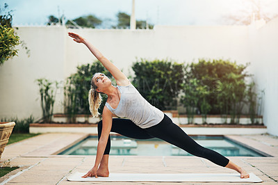 Buy stock photo Shot of a young woman doing yoga poolside