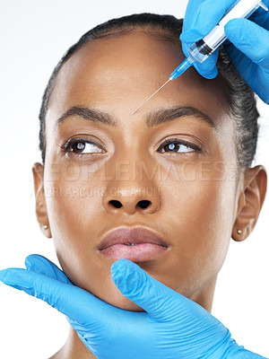 Buy stock photo Studio closeup of an attractive young woman receiving a botox injection in her face while standing against a white background
