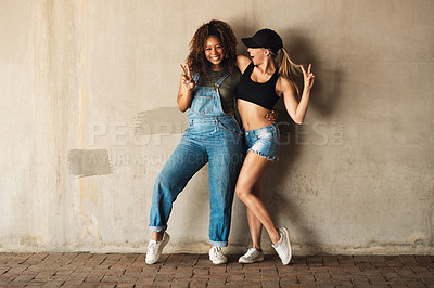 Buy stock photo Portrait of two cheerful young women posing for for a photo while leaning against a wall outside during the day