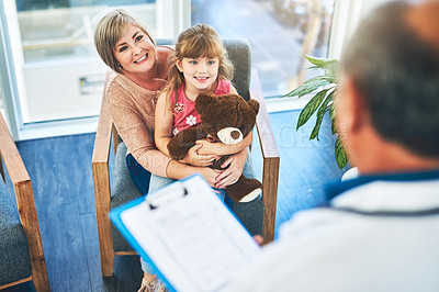 Buy stock photo Shot of an adorable little girl visiting the doctor with her mother