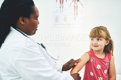 Buy stock photo Shot of a young female doctor performing a checkup on little girl