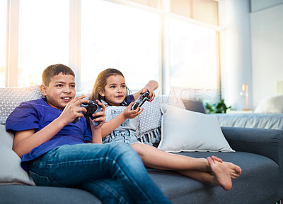 Buy stock photo Shot of two young children sitting on a sofa and playing video game at home