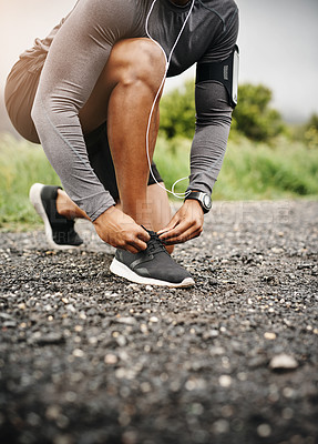Buy stock photo Closeup shot of a sporty man tying his shoelaces while exercising outdoors