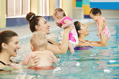 Buy stock photo Shot of a group of mothers enjoying themselves with their babies at swimming class