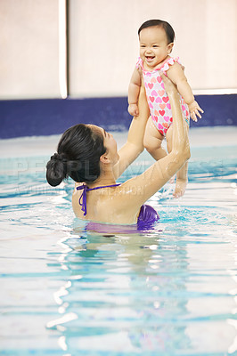 Buy stock photo Shot of a little baby learning to swim in an indoor pool