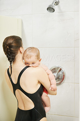 Buy stock photo Shot of a mother giving her baby a shower after swimming in a pool together