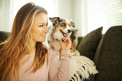 Buy stock photo Shot of a young woman spending quality time with her dog at home