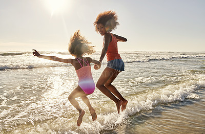 Buy stock photo Rearview shot of a mother and her little daughter having fun at the beach