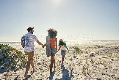 Buy stock photo Rearview shot of a little girl and her parents spending time together at the beach