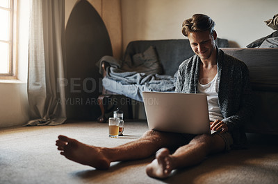 Buy stock photo Shot of a handsome young man using his laptop while sitting on the floor at home