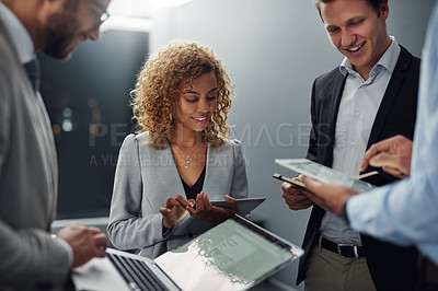 Buy stock photo Cropped shot of a group of businesspeople using digital devices while brainstorming in an office