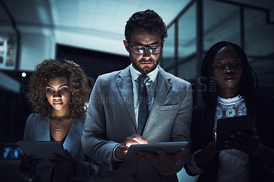 Buy stock photo Cropped shot of a group of businesspeople working late on digital tablets in an office