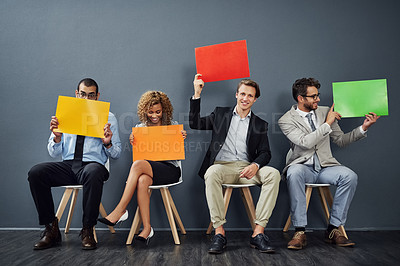 Buy stock photo Full length shot of a group of young creative businesspeople holding up blank placards in their office