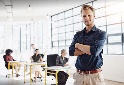 Buy stock photo Portrait of a happy designer posing in the office while his colleagues work in the background