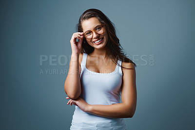Buy stock photo Shot of a beautiful young woman posing with reading glasses against a blue background