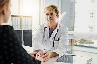 Buy stock photo Cropped shot of an attractive mature female doctor holding a patient's hand in comfort in her office in the hospital